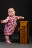A baby girl standing. A baby girl standing by a box looking to the left royalty free stock images