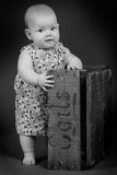 A baby girl standing. A baby girl standing by a box looking towards the camera royalty free stock image