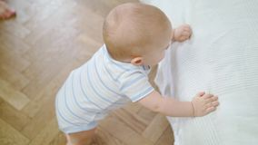 Baby girl standing on the floor at the bed stock footage