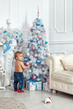 Baby girl standing near the Christmas tree. And holding decorations Stock Photography