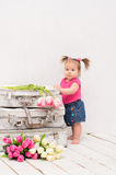 Baby girl standing near old vintage suitcases. On white wooden floor in  painted Stock Images