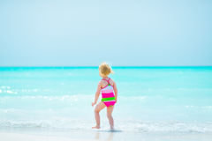 Baby girl standing on sea coast Stock Images