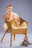 Baby girl stands on armchair. Baby girl stands on wicker armchair Royalty Free Stock Images