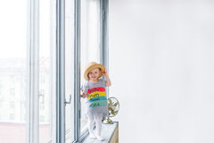 Baby girl in a straw hat and a beautiful children`s shirt costs on a window sill. Stock Photo