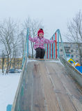 Baby girl on the street riding the ice slides in the winter Stock Photo