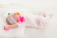 Baby girl stretches in his sleep lying in bed Royalty Free Stock Images