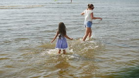 Baby girl in a striped dress and runs sea. And squirts mother water stock video