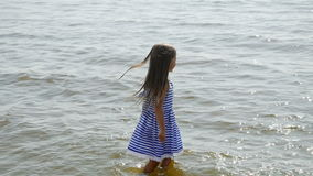 Baby girl in a striped dress and runs sea. And squirts mother water stock footage