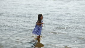 Baby girl in a striped dress and runs. To the sea the ocean stock video footage