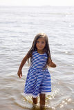 Baby girl in a striped dress and runs. To the sea the ocean Royalty Free Stock Photography