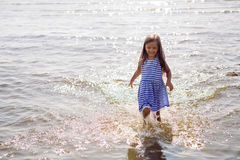 Baby girl in a striped dress and runs. To the sea the ocean Royalty Free Stock Photo
