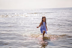 Baby girl in a striped dress and runs. To the sea the ocean Stock Photo