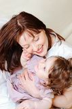 Baby girl strokes her mother Stock Images