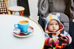 Baby girl in stroller near the table of Parisian outdoor cafe with cup of coffee on it. Going out with kids concept royalty free stock photos