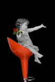 Baby girl on a stylish stool. Baby girl with a rose sitting on a red swivel chair - vintage effect with selective desaturation - isolated on black royalty free stock image