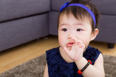 Baby girl sucking finger. With navy blue dressing Stock Photo