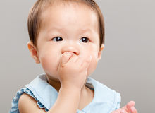 Baby girl sucking her finger into mouth. With gray background Royalty Free Stock Images