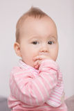 Baby girl sucking her fingers. Easing the pain of teething Stock Photos