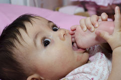 Baby Girl sucking her Toe Stock Photo