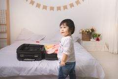 Baby girl with suitcase baggage and clothes ready for traveling. On vacation Stock Photos
