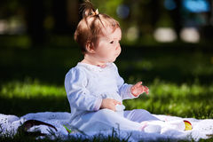 Baby girl in summer dress sitting in the green meadow in the city park. Cute little girl in the beautiful white clothing. Horizontal photo. Sunshiny summer day Royalty Free Stock Photography