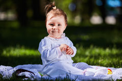 Baby girl in summer dress sitting in the green meadow in the city park. Cute little girl in the beautiful white clothing. Horizontal photo. Sunshiny summer day Royalty Free Stock Photo