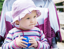 Baby girl in the sun hat posing with blue ball Royalty Free Stock Photos