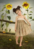 Baby girl in sunflowers. Little girl in yellow sundress in the field among sunflowers royalty free stock photography