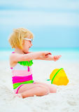 Baby girl in sunglasses applying sun block creme Stock Photography