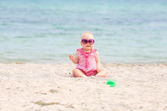 Baby girl in sunglasses on beach Stock Photos