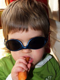 Baby girl with sunglasses and carrot Royalty Free Stock Photography