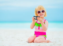 Baby girl in sunglasses with photo camera Royalty Free Stock Photography