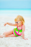 Baby girl in sunglasses playing with sand Royalty Free Stock Photography