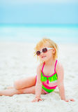 Baby girl in sunglasses sitting on beach Royalty Free Stock Images