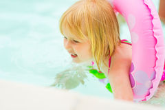 Baby girl with swim ring swimming in pool Stock Photo