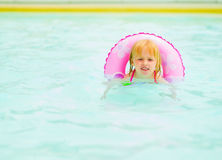 Baby girl with swim ring swimming in pool Stock Photos