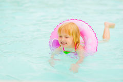 Baby girl with swim ring swimming in pool. Happy baby girl with swim ring swimming in pool Royalty Free Stock Photography