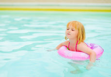 Baby girl with swim ring in swimming pool Stock Images