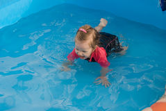 The baby girl swiming in pool Royalty Free Stock Image