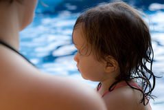 The baby girl swiming in pool Stock Photos