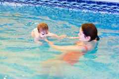 Baby girl swimming with her mother in a pool. LIttle baby girl swimming with her mother in a pool royalty free stock photography
