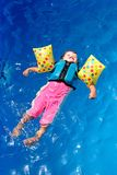 Baby girl in swimming pool. Baby girl floating on top of swimming pool in flotation jacket and arm bands Royalty Free Stock Photos