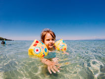 Baby girl swimming in sea. Water royalty free stock photo