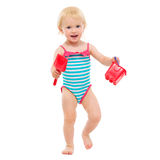 Baby girl in swimsuit holding bucket and shovel Royalty Free Stock Images
