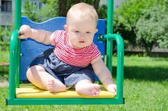Baby girl on a swing. Little baby girl in a striped dress sitting on a swing and looks with interest stock image
