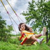 Baby girl in swing outdoors Royalty Free Stock Photography