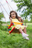 Baby girl in swing outdoors Royalty Free Stock Images