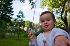 Baby girl in swing. Little baby girl in wooden swing taking a selfie Stock Image