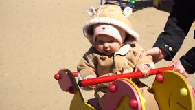 Baby girl swingin on horse swing in day. Baby girl swingin on horse swing in kids park in day stock footage