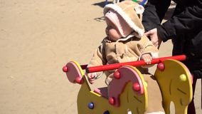 Baby girl swingin on horse swing. In kids park stock video footage